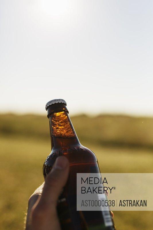 Man holding beer bottle on field