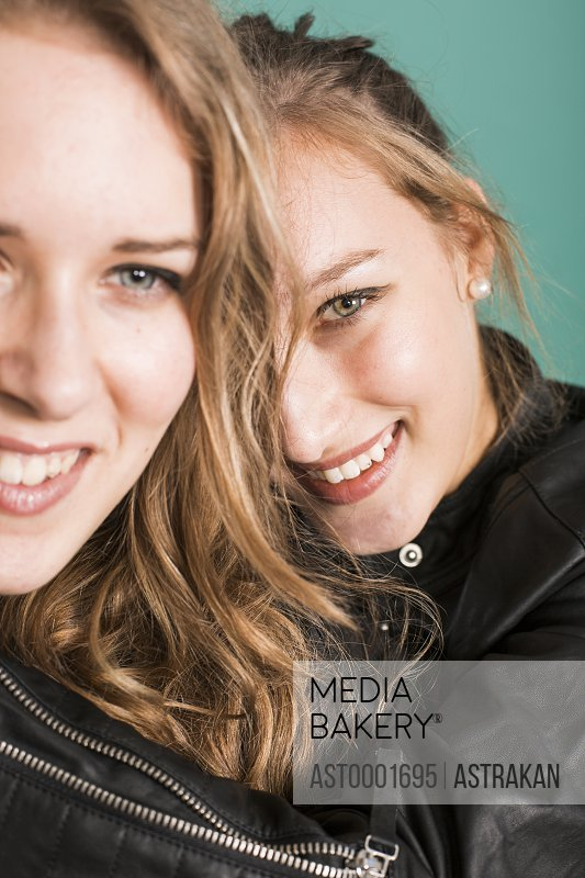 Portrait of happy fashion model with sister against green background