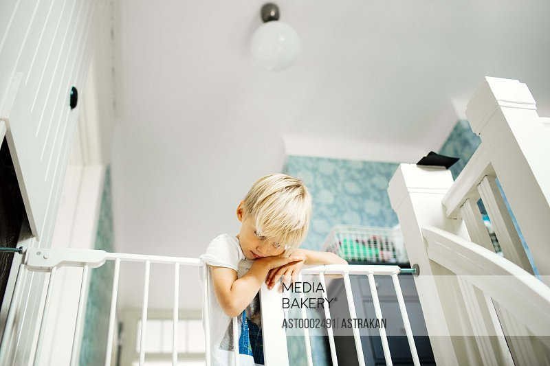 Low angle view of boy leaning on railing at home