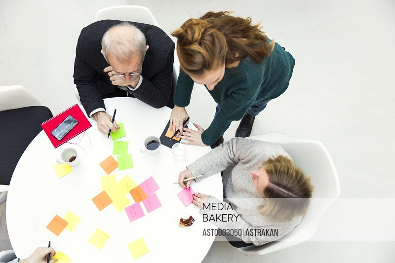 High angle view of business people with adhesive notes at table in creative office