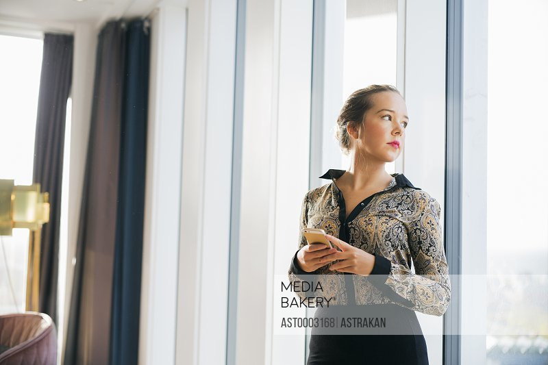 Confident businesswoman standing against window at hotel