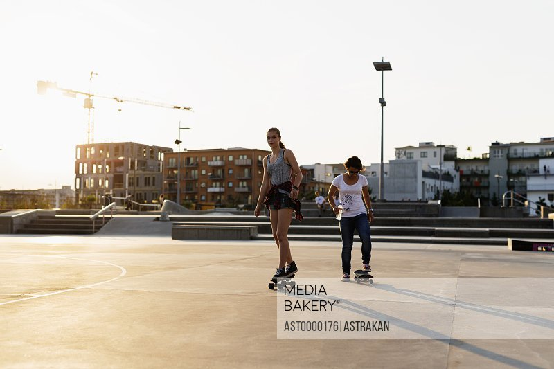 Full length of teenage girls skateboarding in skate park