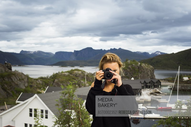 Woman photographing through digital camera against mountains