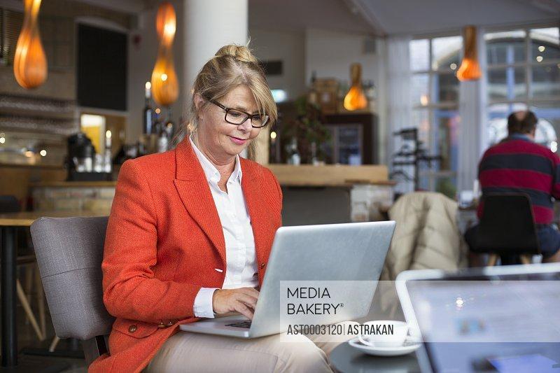 Smiling businesswoman using laptop in restaurant