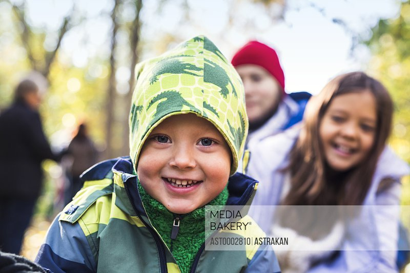 Portrait of happy boy wearing warm clothing with family in background at forest