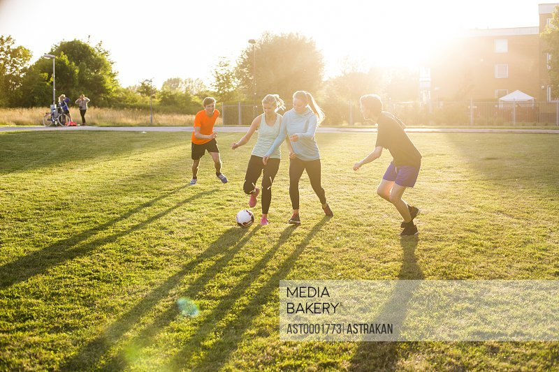 Male and female friends playing soccer at park during sunset