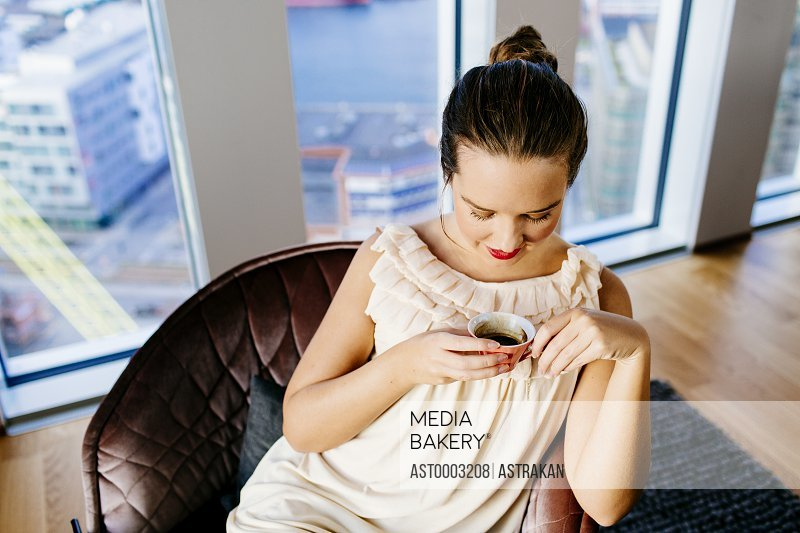 High angle view of woman with coffee sitting on chair at hotel room