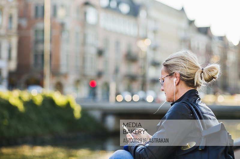 Mature woman sitting and using smart phone outdoors