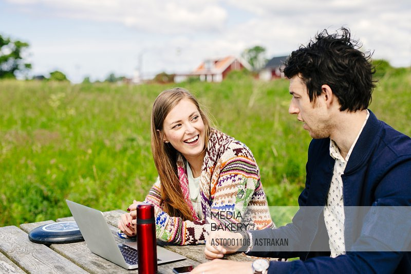 Friends smiling while discussing over laptop at table on field