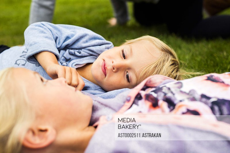 Boy with sister relaxing in yard