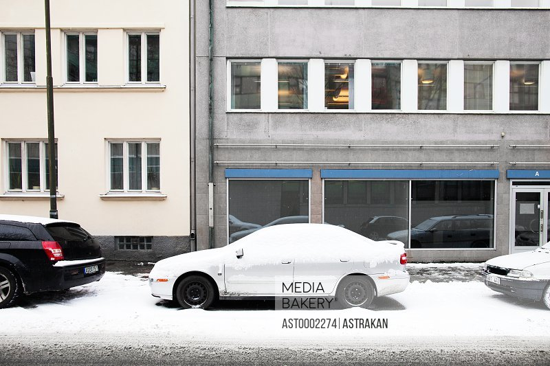 Cars covered with snow on street against city buildings