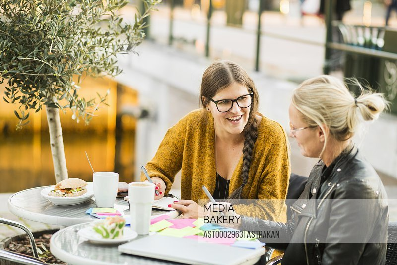 High angle view of woman smiling while looking at colleague at sidewalk cafe