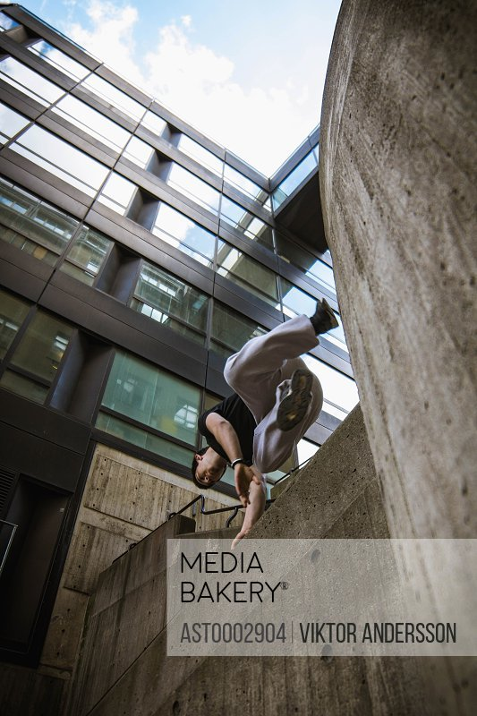 Low angle view of man jumping over retaining wall by modern building