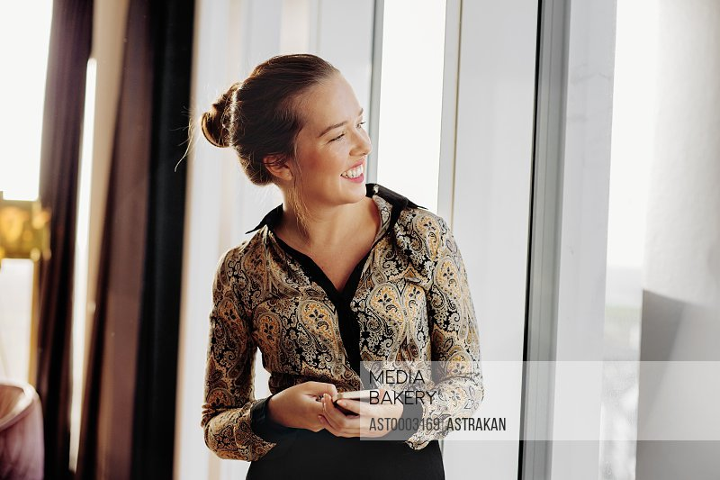 Smiling businesswoman holding smart phone while standing at hotel room