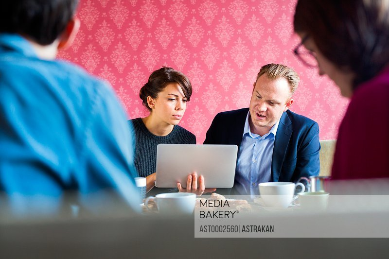 Business people using laptop during meeting in office
