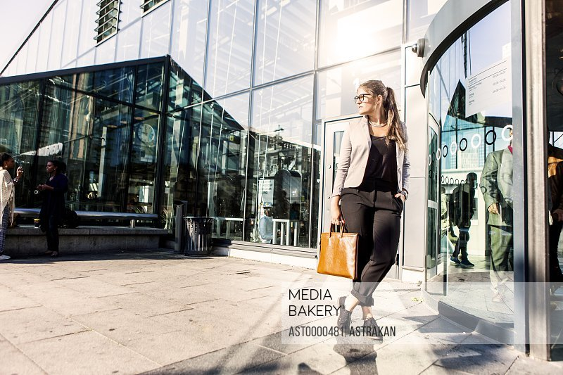 Businesswoman looking away while standing outside railroad station