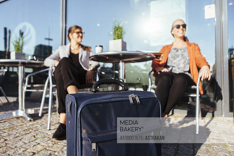 Businesswomen sitting on chair at sidewalk cafe with luggage