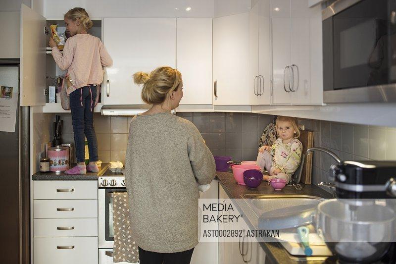 Family preparing pancake together in kitchen