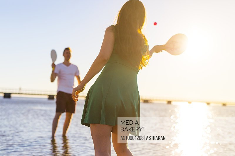 Young couple playing with racquet and ball