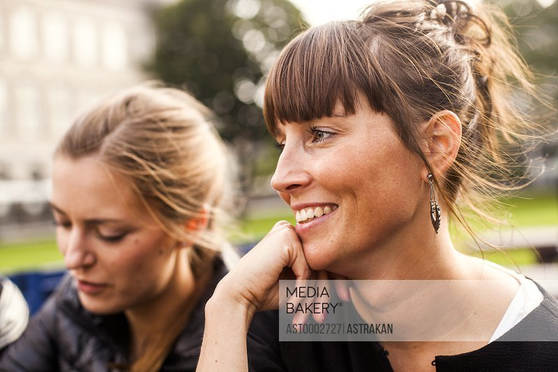 Happy woman sitting with female friend at park