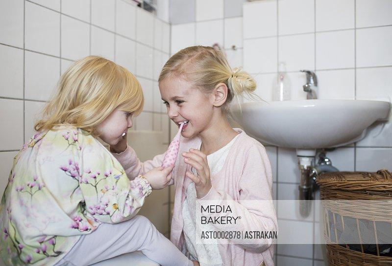 Sisters brushing each others teeth in bathroom