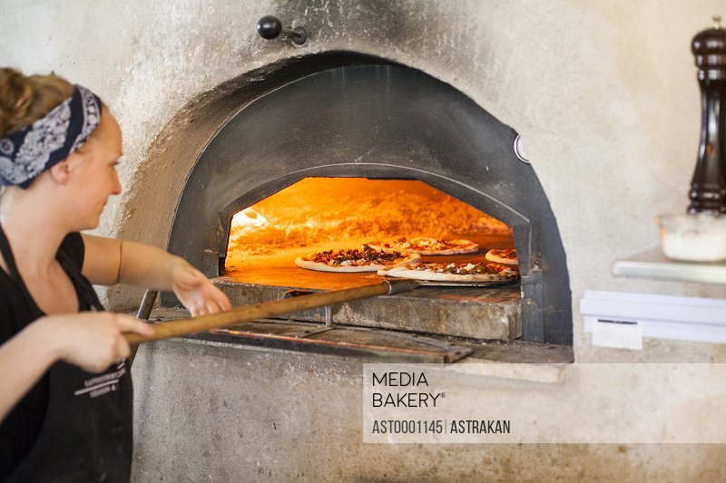 Female chef putting pizza in wood fired oven