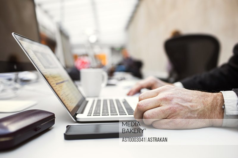 Cropped image of senior businessman using laptop at table in creative office