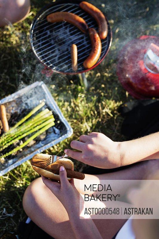 High angle view of woman holding hotdog