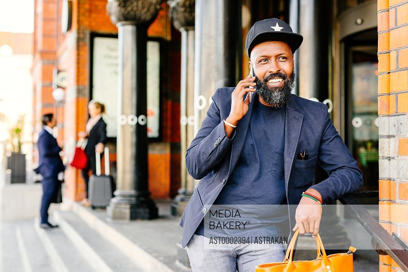 Smiling businessman using smart phone outside railroad station