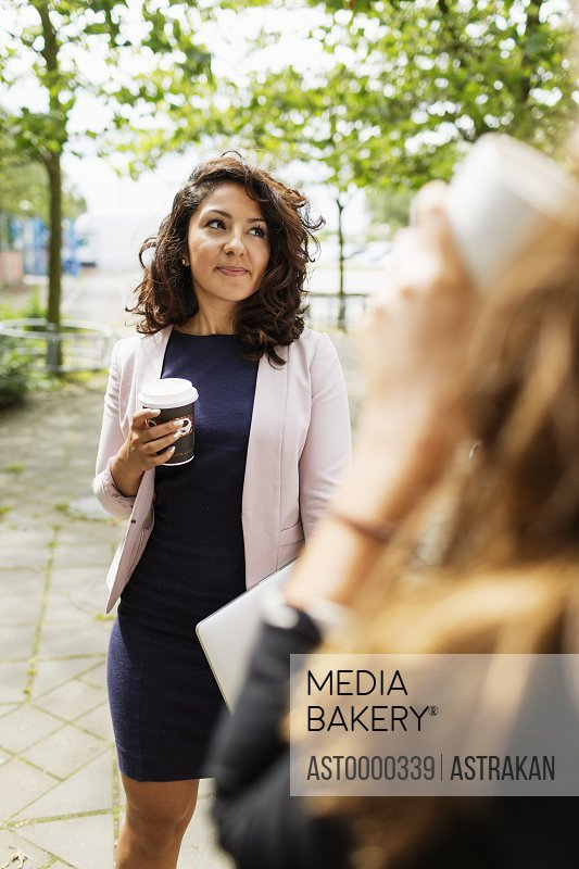Young businesswoman holding coffee while standing with colleague outdoors