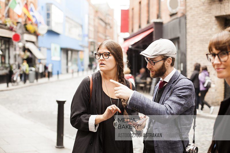 Man talking to female friend on city street