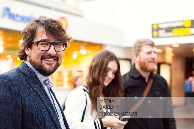 Portrait of happy businessman with colleagues at railroad station