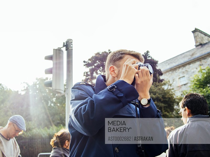 Man photographing in city against clear sky