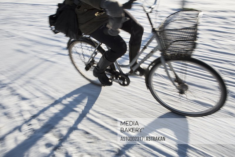 Low section of person riding bicycle on snow covered street