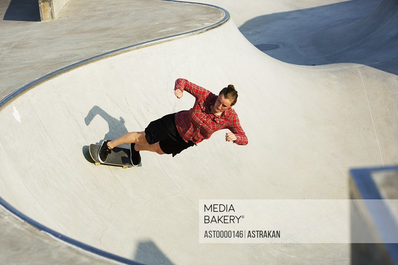 High angle view of woman skateboarding on ramp in skate park