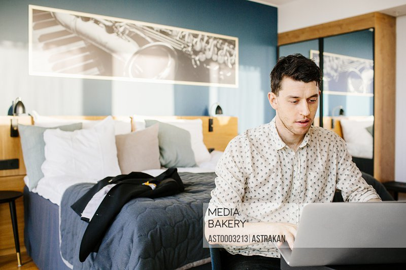 Businessman using laptop against bed at hotel room