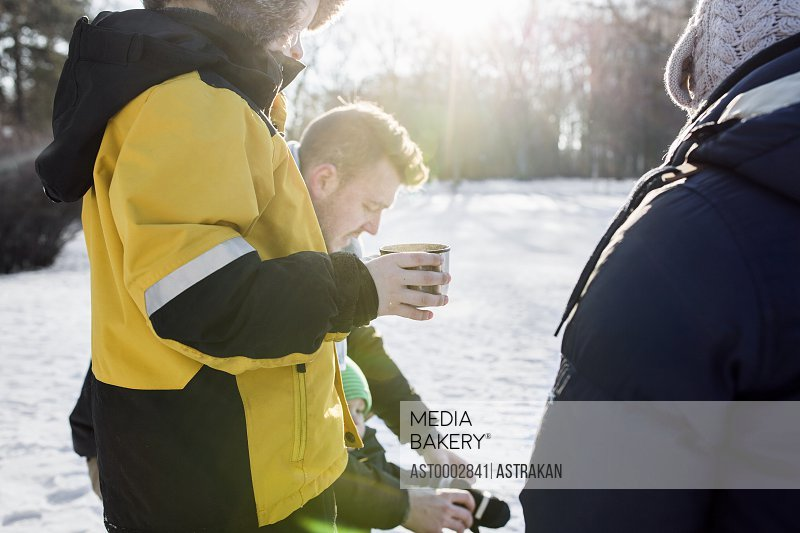Midsection of boy having coffee while standing by family on snowy field