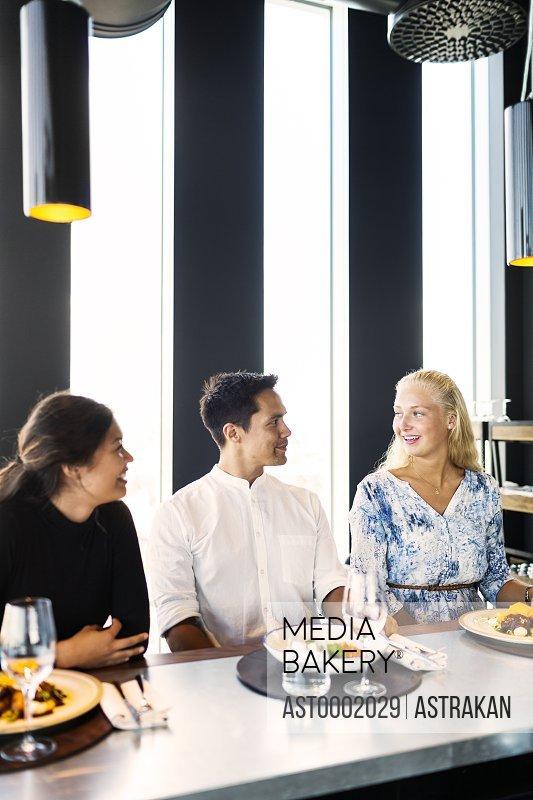 Happy young friends having conversation in restaurant