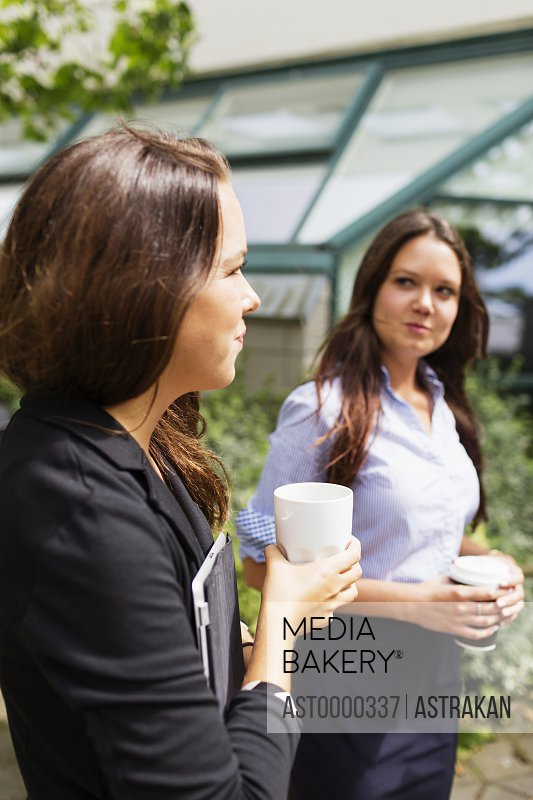 Businesswomen holding coffee while standing outdoors