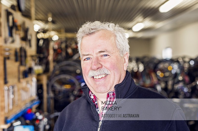 Portrait of happy senior owner in bicycle shop
