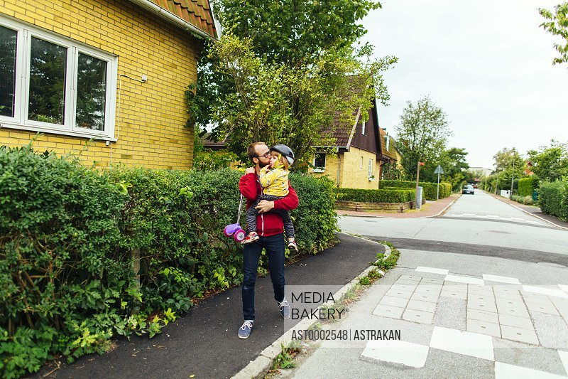 Full length of man carrying daughter and push scooter on sidewalk