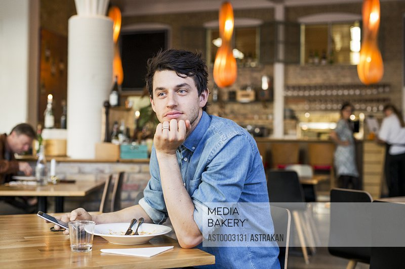 Businessman looking away while sitting at restaurant