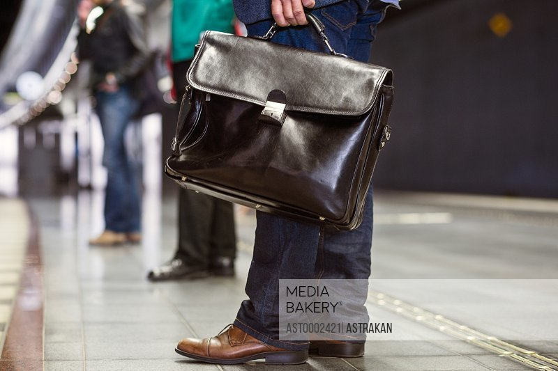 Low section of businessman carrying briefcase while standing on railroad station platform