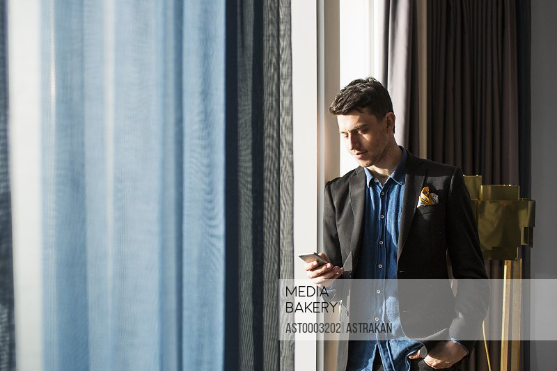 Businessman using phone while standing by window in hotel room