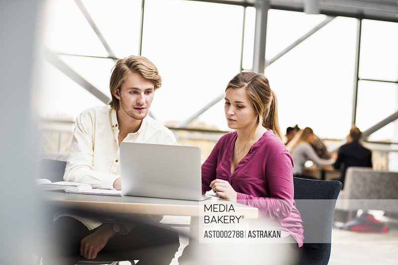 Young male and female friends using laptop at table in university