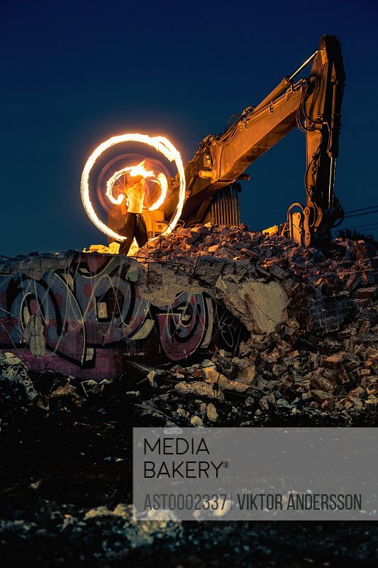 Man doing light painting on broken building ruins by bulldozer at night