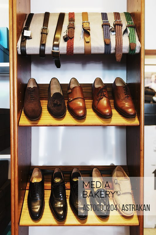 Leather shoes and belts arranged on shelves at clothing store