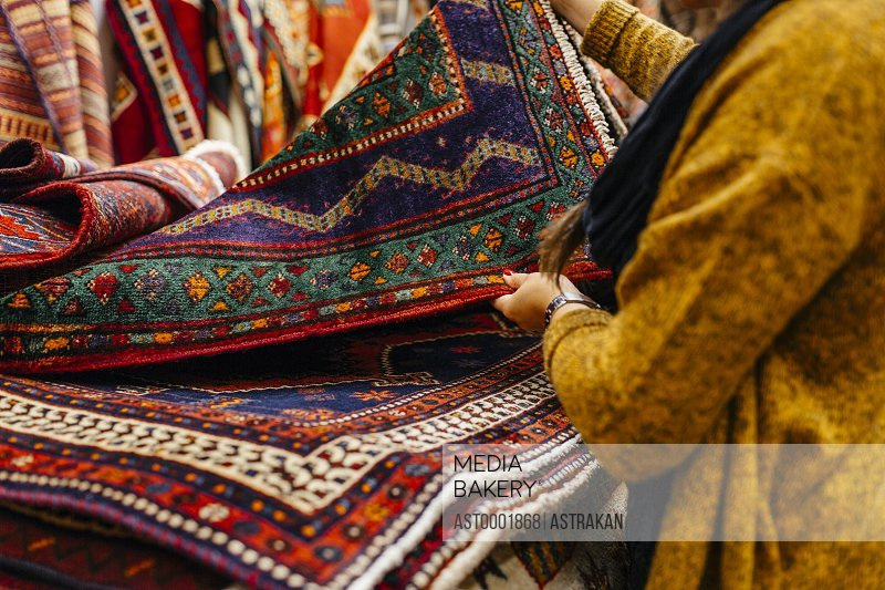 Midsection of young woman shopping for rugs in furniture warehouse