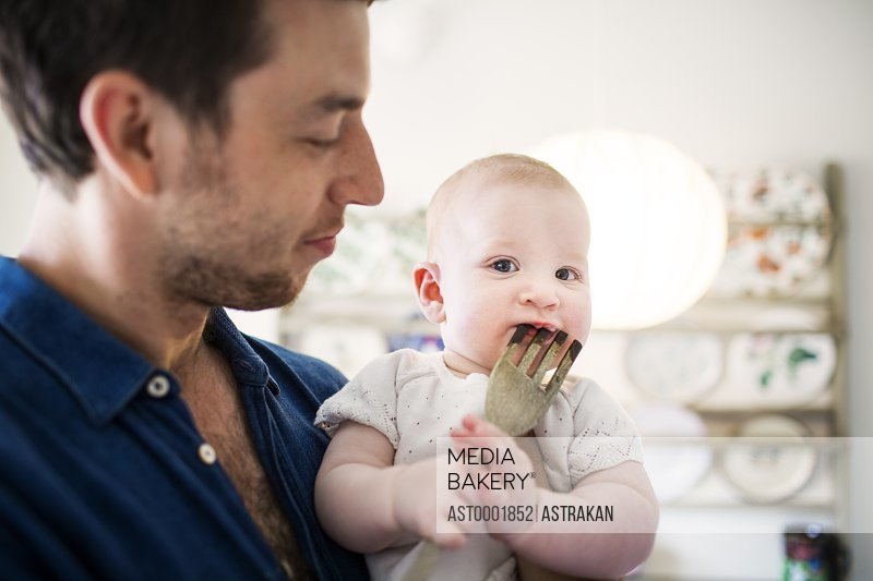 Portrait of cute baby girl biting wooden fork while father looking at her in kitchen