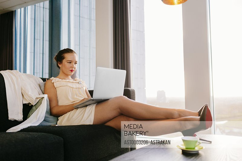 Classy businesswoman using laptop while sitting on sofa at hotel room